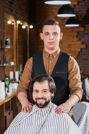 handsome young barber standing behind client at workplace Фото со стока
