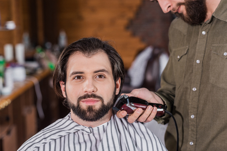 barber shaving happy handsome client with Hair Clipper Фото со стока