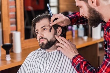 young barber in plaid shirt shaving man with Hair Cutting Machine Фото со стока