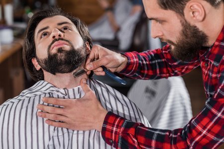 close-up shot of young barber shaving man with Hair Cutting Machine Фото со стока - 109417221