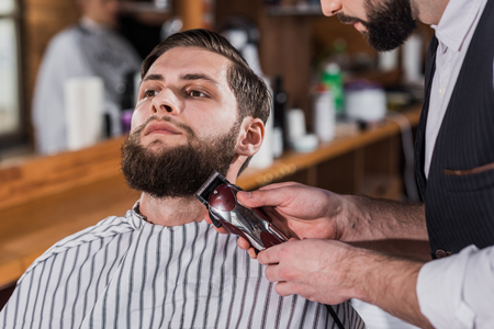 close-up shot of barber shaving man with Hair Cutting Machine Фото со стока - 109417231