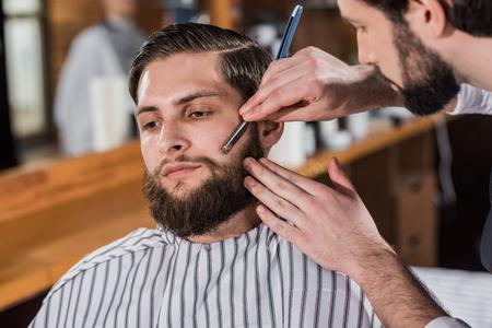 close-up shot of barber shaving man with straight razor Фото со стока - 109417240