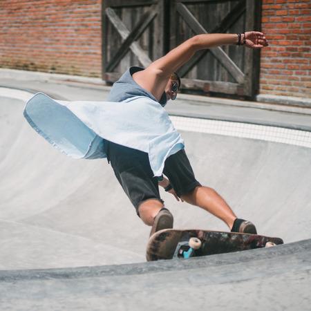 young skater skating on longboard at skatepark