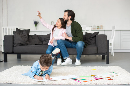 happy father and daughter sitting on sofa and taking selfie with smartphone while little boy drawing on carpet at home Фото со стока - 109417359