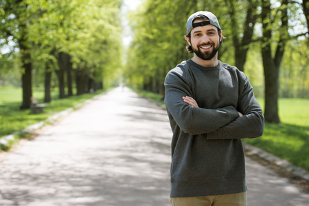 smiling man standing with crossed hands on path in park Stock Photo - 109417419