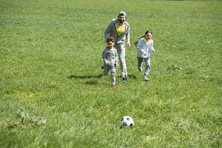 happy sportive family playing football on grassy meadow