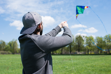 rear view of man flying kite on grassy meadow in park 스톡 콘텐츠
