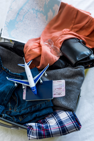 travel bag with clothes, passport, air ticket, map and airplane model Stock Photo