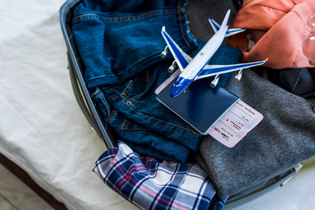 close up of suitcase with clothes, passport, air ticket and airplane model