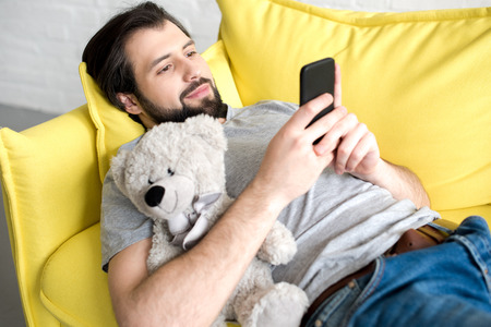 smiling young man using smartphone while lying on sofa and hugging teddy bear