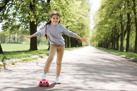 little child with skateboard on path in park