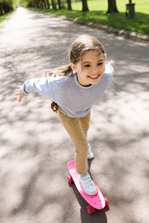 smiling little child riding on skateboard in park