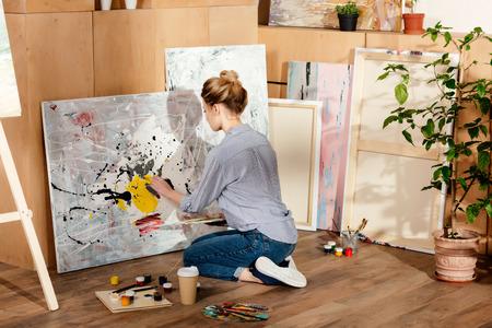 Vue arrière de la peinture de jolie fille en studio d'art