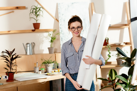 portrait of smiling stylish female artist in eyeglasses holding canvases Stok Fotoğraf