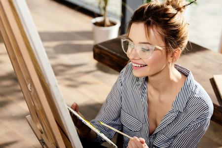 smiling stylish female artist in eyeglasses painting on easel Stok Fotoğraf