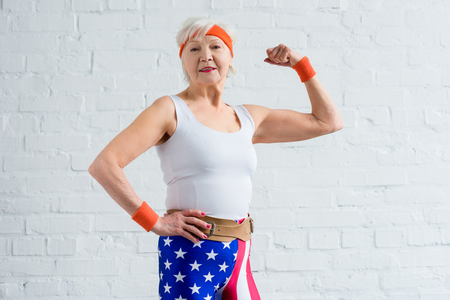 happy senior sportswoman showing biceps and smiling at camera