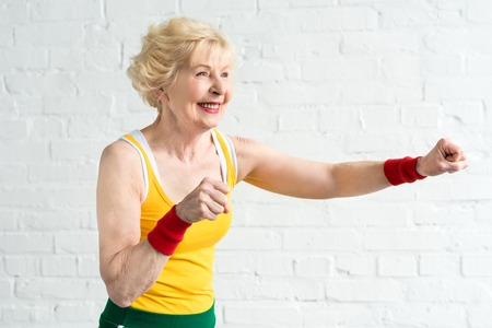 happy senior woman in sportswear boxing and looking away