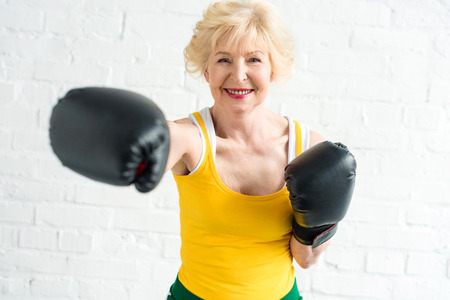 happy senior woman in boxing gloves training and smiling at camera