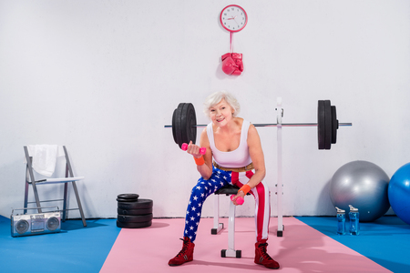 sporty senior lady exercising with dumbbells and smiling at camera Stock Photo