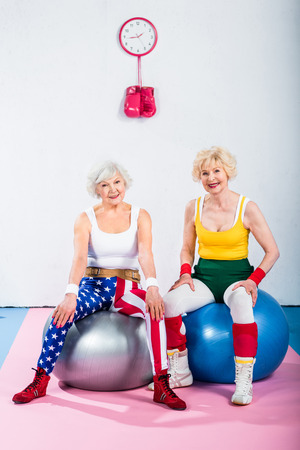sporty senior women in sportswear sitting on fitness balls and smiling at camera