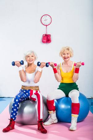 senior women in sportswear training with dumbbells while sitting on fitness balls and smiling at camera
