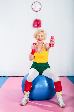 happy senior woman in sportswear sitting on fitness ball and exercising with dumbbells 版權商用圖片