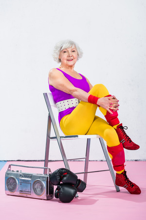 happy senior sportswoman sitting near tape recorder with boxing gloves and smiling at camera