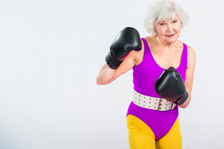 sportive senior lady boxing and smiling at camera isolated on grey