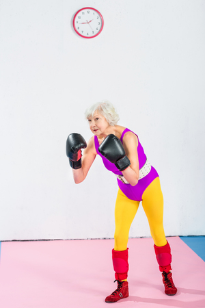 full length view of senior woman in sportswear and boxing gloves training and looking away Stock Photo