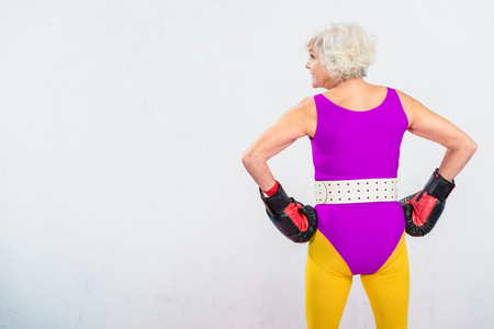 back view of sporty senior woman in boxing gloves standing with hands on waist isolated on grey Stock Photo
