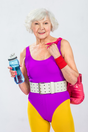 beautiful smiling senior sportswoman holding bottle of water and boxing gloves