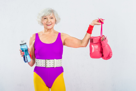 happy senior sportswoman holding bottle of water and boxing gloves Stock Photo