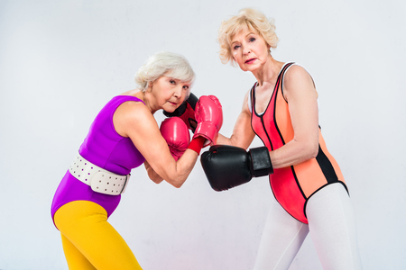 side view of senior sportswomen in boxing gloves training and looking at camera isolated on grey