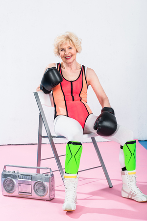 sporty senior woman in boxing gloves sitting with tape recorder and smiling at camera Stock Photo