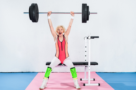 excited senior sportswoman lifting barbell