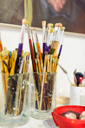 painting brushes in glasses on table in workshop