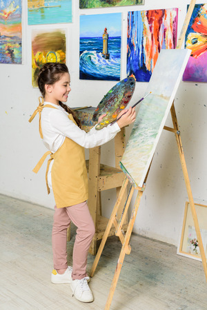 side view of preteen kid painting in workshop of art school