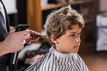cropped shot of barber spraying hair of adorable little kid at kids barbershop
