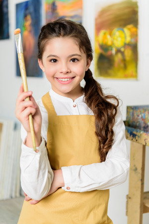 smiling kid standing with painting brush in workshop of art school