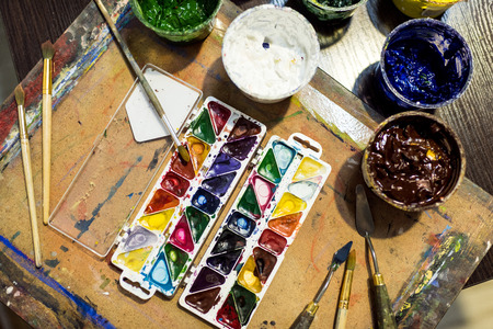 top view of poster paints and watercolor paints on wooden table in workshop