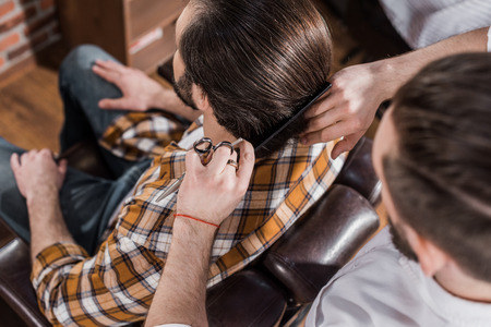 high angle view of barber combing hair of customer at barbershop Фото со стока - 109464423
