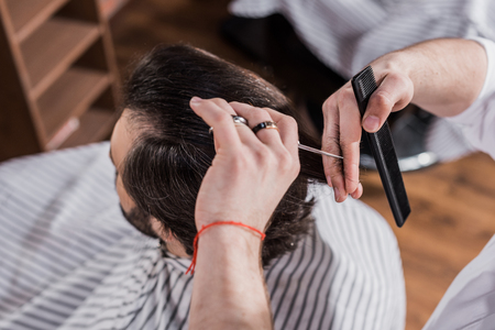 high angle view of barber cutting hair of customer with scissors Фото со стока