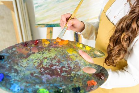 beschnittenes Bild des Kindes, das Ölfarben von der Palette in der Werkstatt der Kunstschule nimmt Standard-Bild