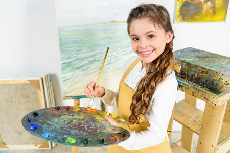 kid holding painting brush and palette in workshop of art school