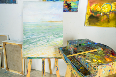 canvas on easel and paintings on wall in workshop 스톡 콘텐츠