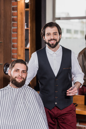 handsome bearded barber with client at barbershop