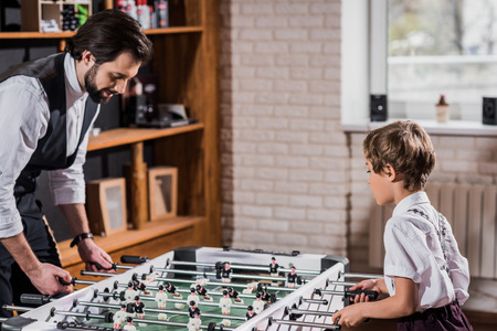 handsome bearded father and little son playing table football