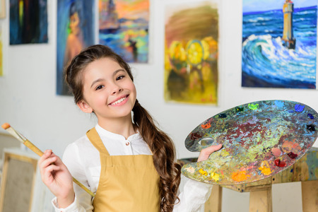 smiling kid standing with palette and painting brush in workshop of art school