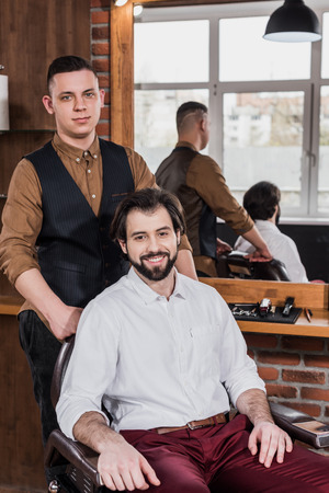 happy young customer and barber in barbershop looking at camera