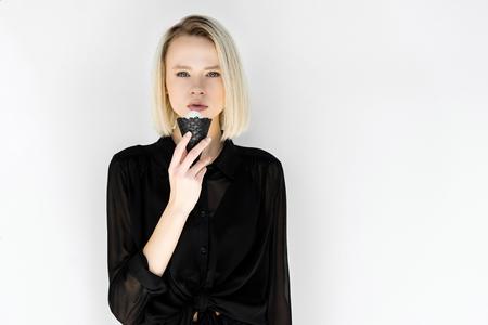 Jolie femme blonde élégante en vêtements noirs, manger de la crème glacée en cône noir isolé sur blanc Banque d'images